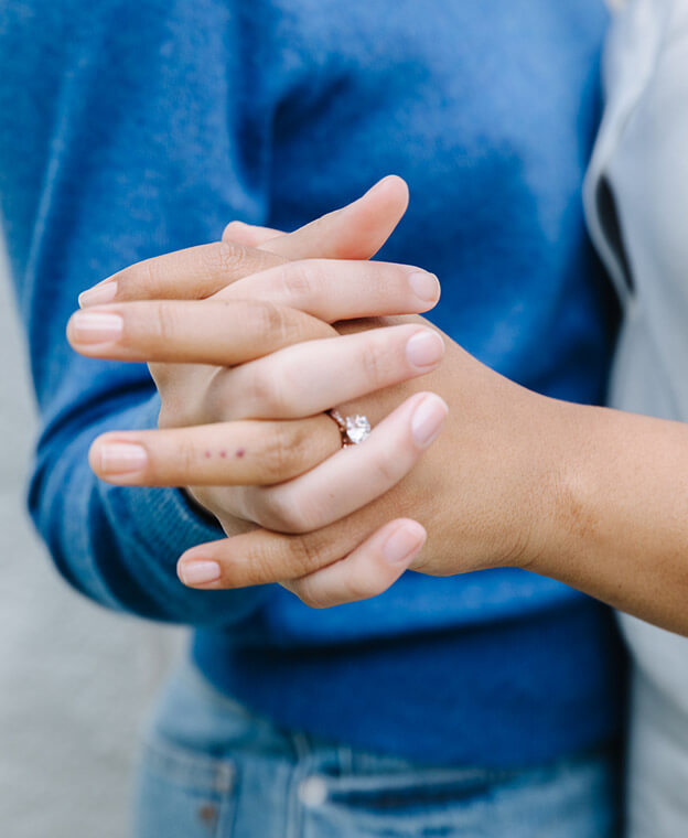 Two hands interlocked, one wearing a lab-grown diamond ring, with the couple embracing in the background.